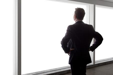 中年実業家明るいオフィスの窓の外を見て、考えて