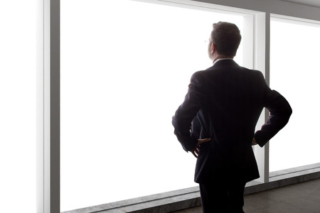 out of business: Middle aged businessman looking out a bright office window and thinking