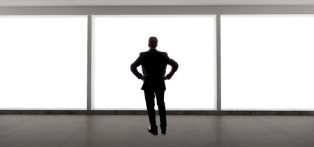 Middle aged businessman looking out a bright office window and thinking photo