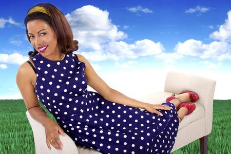 polka dot dress: black female in a vintage polka dot dress in a surreal outdoors setting Stock Photo