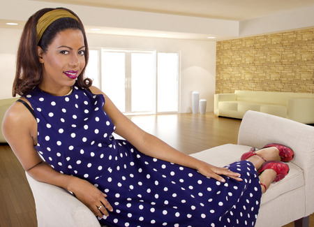 woman closet: black female sitting on a lounge at home in a blue polka dot dress