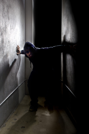 hoodlum: hooded criminal stalking in the shadows of a dark street alley