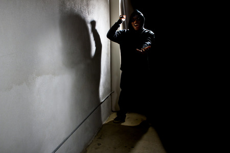 intimidate: hooded criminal stalking in the shadows of a dark street alley