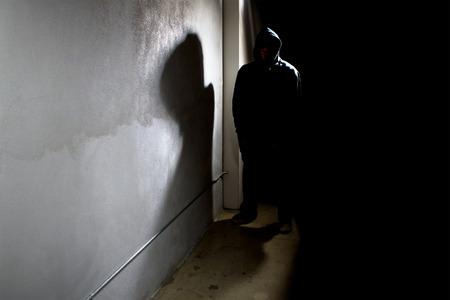 ladron: acecho criminal encapuchado en las sombras de un callejón calle oscura
