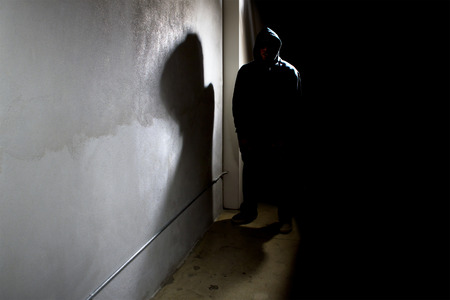 criminal: hooded criminal stalking in the shadows of a dark street alley