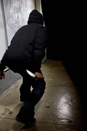 dark alley: hooded criminal with a knife hiding in the shadows of a street alley