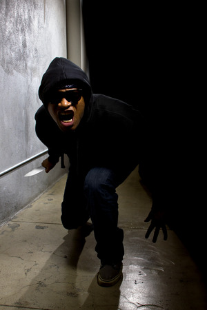 hooded criminal with a knife hiding in the shadows of a street alley