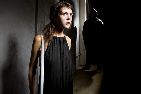 ladron: acecho criminal una mujer sola en un callejón calle oscura Foto de archivo