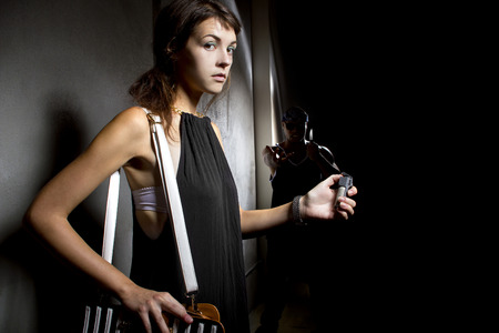 defensa personal: mujer que usa un pepperspray para la autodefensa contra asaltante en un callejón oscuro
