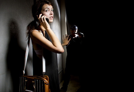woman calling 911 for help in an alley while a criminal is stalking her Foto de archivo