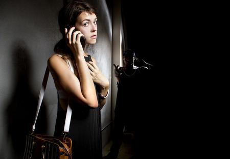Frau ruft um Hilfe 911 in einer Gasse, während ein Verbrecher ist Stalking ihr Standard-Bild - 42184939