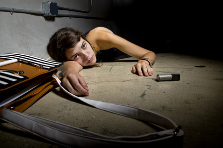 robbed: female crime victim laying on the street floor with a can of mace Stock Photo