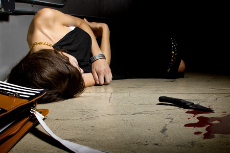 murder scene: female murder victim laying on a dark alley with a bloody knife