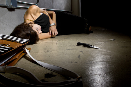mugged: female laying dead on a street alley with a knife murder weapon