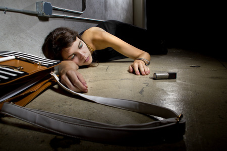 female crime victim laying on the street floor with a can of mace Stock Photo