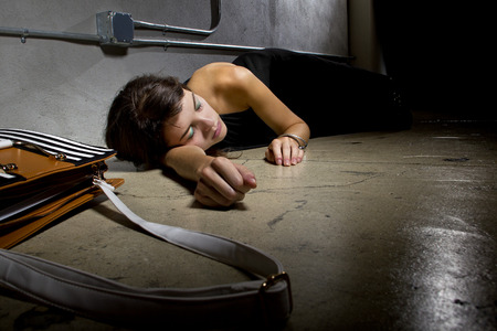 blacked: female crime victim laying on the street floor or passed out drunk Stock Photo