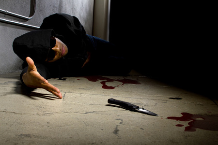 mugging: man in a street alley killed with a knife with blood and murder weapon Stock Photo