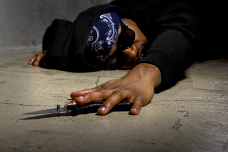 man in a street alley killed with a knife and victim of gang violence Stock Photo