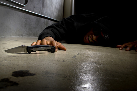 violent: man in a street alley killed with a knife and victim of gang violence Stock Photo