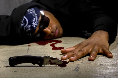 murdered: man in a street alley killed with a knife with blood and murder weapon Stock Photo