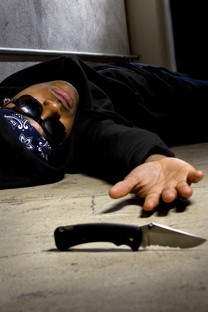 hoodlum: man in a street alley killed with a knife and victim of gang violence Stock Photo