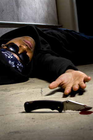 hoodlum: man in a street alley killed with a knife with blood and murder weapon Stock Photo