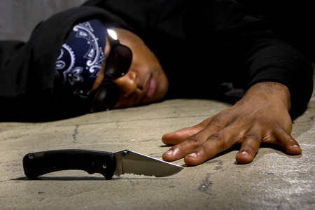 mugging: man in a street alley killed with a knife and victim of gang violence Stock Photo