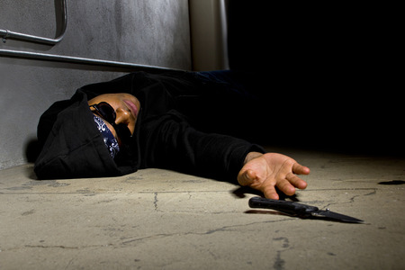murdered: man in a street alley killed with a knife and victim of gang violence Stock Photo