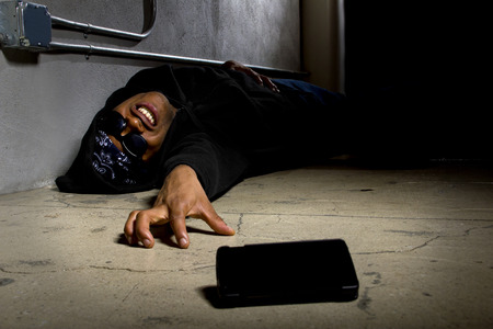 Assaulted gangster calling for help or medical emergency with a cell phone Stock Photo