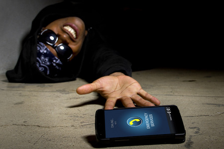 robbed: Assaulted gangster calling for help or medical emergency with a cell phone Stock Photo