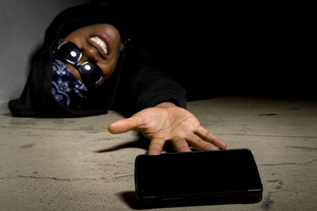 calling for help: Assaulted gangster calling for help or medical emergency with a cell phone Stock Photo
