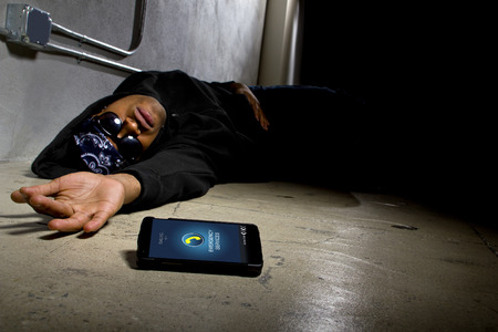 mugged: Assaulted gangster calling for help or medical emergency with a cell phone Stock Photo