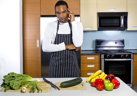 how to: black man learning how to cook in a domestic kitchen with fruits and vegetables