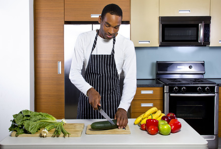 domestic kitchen: black man learning how to cook in a domestic kitchen with fruits and vegetables