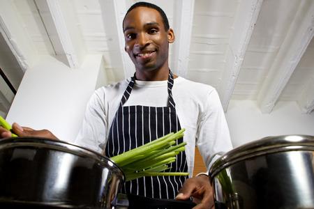 pepe nero: Close up di un giovane uomo di colore che indossa un grembiule e cucina a casa
