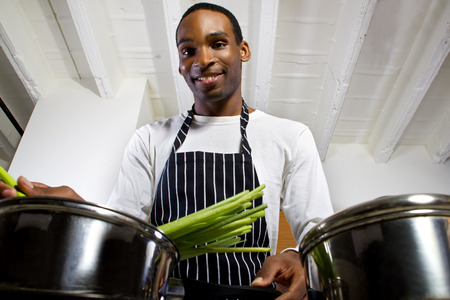 domestic chore: close up of a young black man wearing an apron and cooking at home Stock Photo