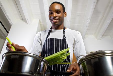 若い黒人男性エプロンを身に着けていると、自宅で料理のクローズ アップ