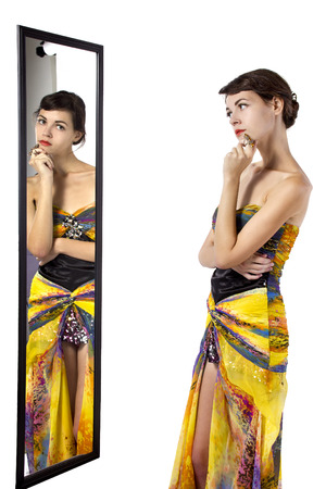 self conceit: Woman wearing a yellow dress looking at her self in a mirror