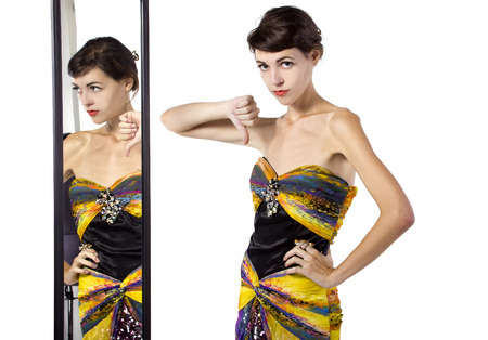 narcissist: woman wearing a dress with her thumbs down while looking at a mirror