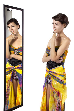 narcissism: Woman wearing a yellow dress looking at her self in a mirror