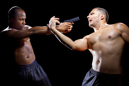 disarm: Martial artist disarming a criminal with a gun or close quarter combat