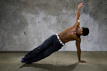 breakdancing: Man demonstrating core balance exercises or yoga on urban background