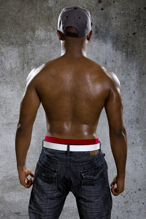 male body: Fit black man in hip hop style clothing flexing back muscles Stock Photo
