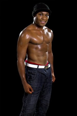 Muscular black male in hip hop style clothing showing abdominal muscles Stock Photo