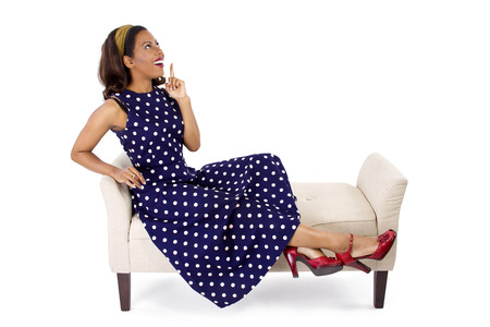 woman on couch: Woman in vintage blue poka dot dress relaxing on a chaise lounge