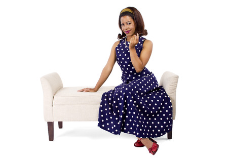 come hither: Woman wearing a blue ploka dot dress on a traditional chaise furniture