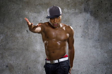 topless jeans: Shirtless muscular black man wearing urban hip hop style clothing on concrete background