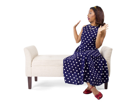 person woman: Woman wearing a blue ploka dot dress on a traditional chaise furniture