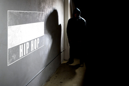 textspace: Hooded hip hop rapper next to wall graffiti with copy space