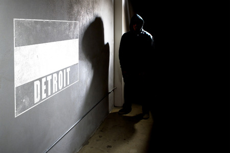 hip hop silhouette: Hooded hip hop rapper next to wall graffiti with copy space
